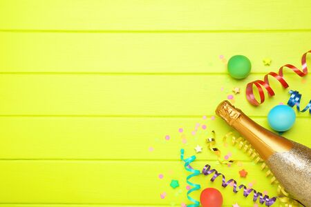 Colorful ribbons with balloons and champagne bottle on green wooden background