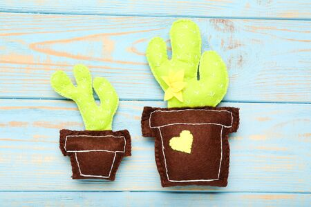Different soft toy of cactuses on blue wooden table