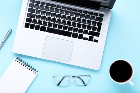 Laptop computer with coffee, glasses and notepad on blue background 版權商用圖片