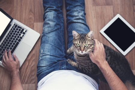 Man sitting on the floor with tablet computer, laptop and beautiful cat