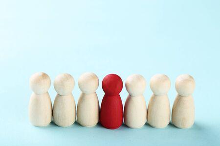 Leader concept. Wooden figures on blue background