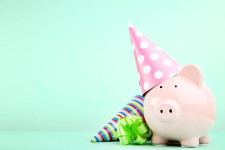 Pink piggy bank with birthday cap on mint background