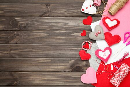 Fabric hearts with ropes, scissors and clothespins on brown wooden table