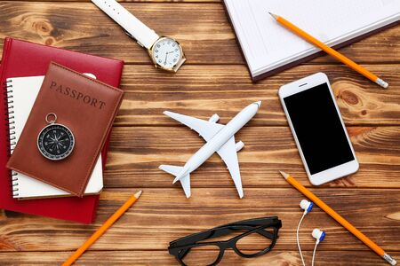 Airplane model with passport, smartphone, pencils, eyeglasses and compass on brown wooden table 版權商用圖片