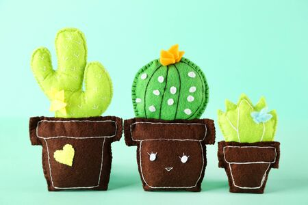 Different soft toy of cactuses on mint background