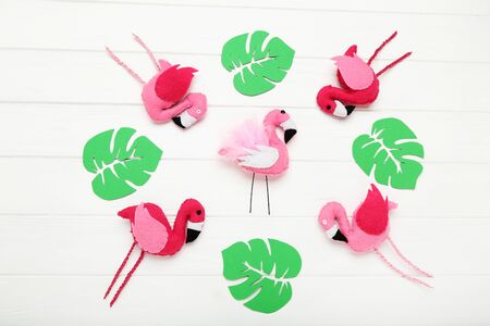 Soft toy of flamingos with green paper leafs on white wooden table 版權商用圖片