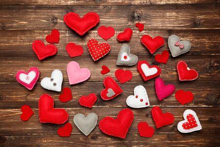 Coeurs en tissu coloré sur une table en bois marron Banque d'images