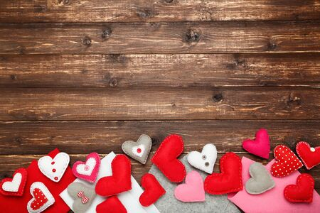 Colorful fabric hearts on brown wooden table 版權商用圖片