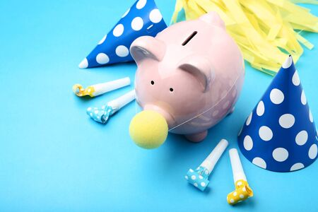 Pink piggy bank with birthday decoration on blue background