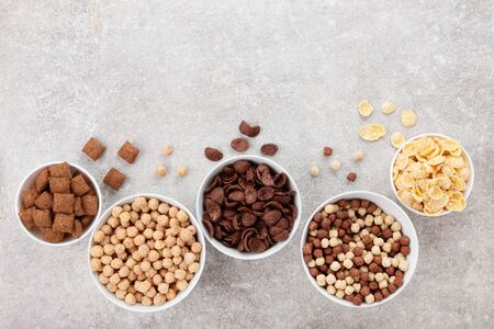 Various corn flakes in bowls on grey background