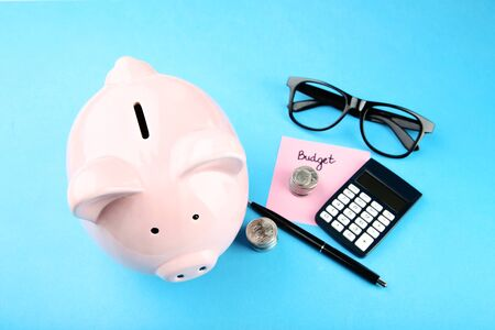 Pink piggy bank with glasses, coins and calculator on blue background