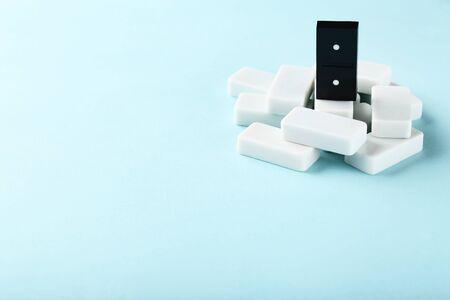 Leader concept. Domino tiles on blue background
