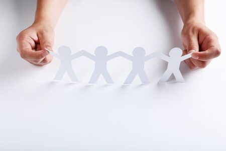Paper chain people with female hands on white background