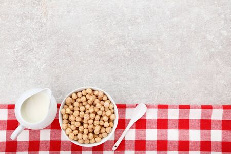 Corn balls with milk in jar and spoon on grey background