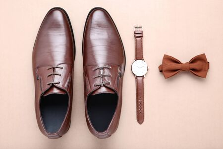 Male leather shoes with wrist watch and bow tie on beige background