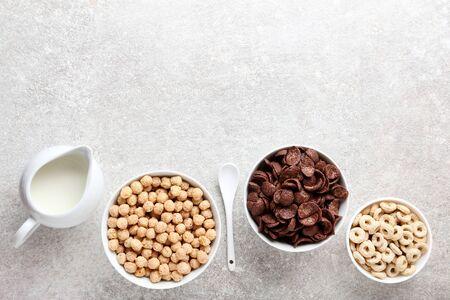 Various corn flakes with milk in jar and spoon on grey background 版權商用圖片