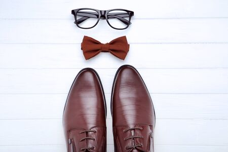Male leather shoes with glasses and bow tie on white background