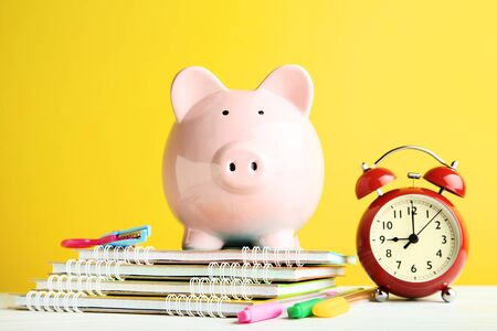 Pink piggy bank with alarm clock and notebooks on yellow background