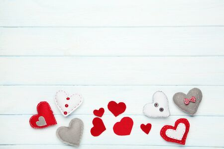 Colorful fabric hearts on white wooden table