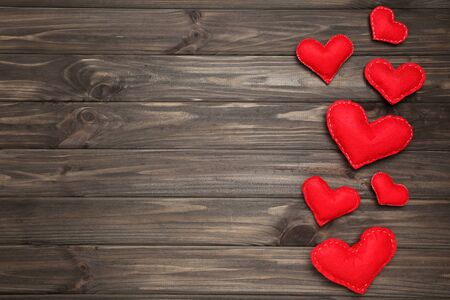 Red fabric hearts on brown wooden table