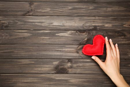 Fabric heart in female hand on brown wooden table