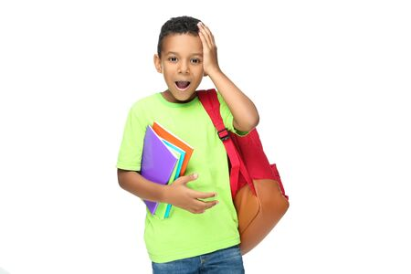 Young African American school boy with notepads and backpack on white background