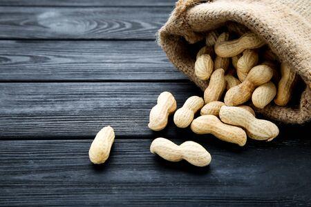 Peanuts in sackcloth on black wooden table Reklamní fotografie - 137798902