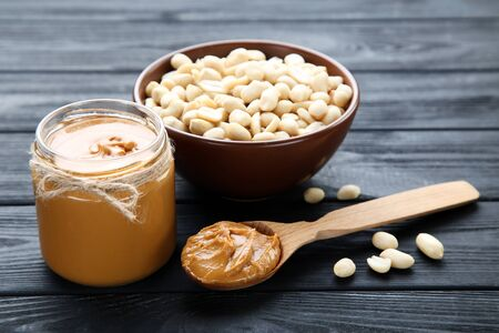 Peanut butter and nuts in bowl on black wooden table