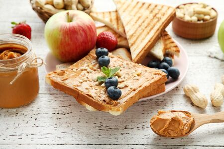 Bread with peanut butter, fruits and nuts on white wooden table