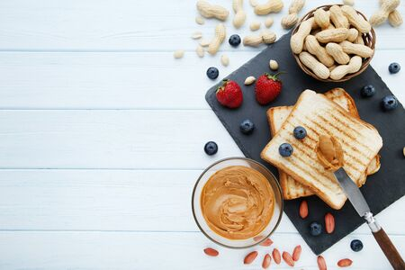 Bread with peanut butter, fruits and nuts on wooden table Reklamní fotografie