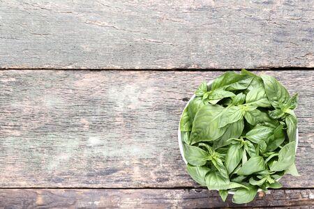 Green basil leafs in bowl on grey wooden table Reklamní fotografie - 137800283