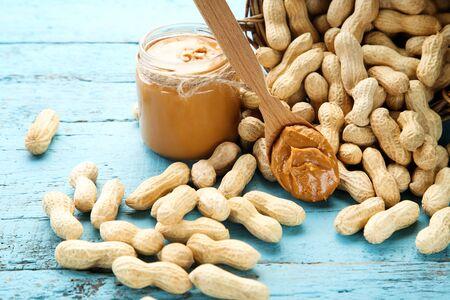 Peanut butter and nuts on blue wooden table Reklamní fotografie