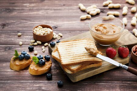 Bread with peanut butter, fruits and nuts on wooden table Reklamní fotografie - 137800288