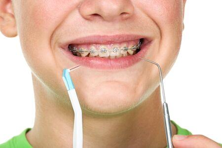 Joven con cepillo de dientes y herramienta de dentista sobre fondo blanco.