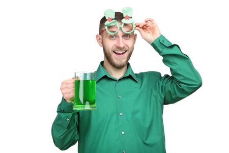 St. Patrick's Day. Young man in glasses with beer on white background