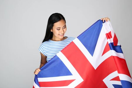 Young woman holding British flag on grey background