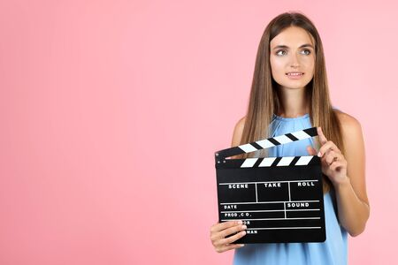 Young woman with black clapper board on pink background