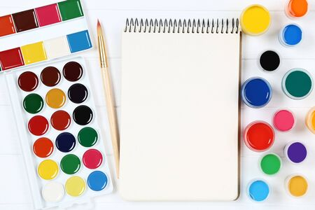 Colorful gouache paints with brush and blank sheet of paper on white wooden table Banco de Imagens - 138296088