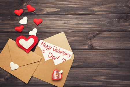 Paper envelopes with hearts and text Happy Valentines Day on wooden table