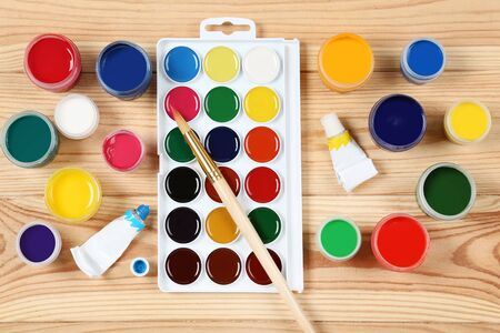 Colorful gouache paints and brush on brown wooden table Banco de Imagens - 138293487