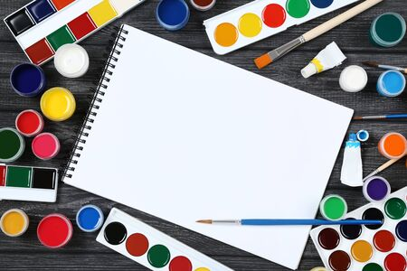 Blank sheet of paper with colorful gouache paints and brushes on black wooden table Banco de Imagens - 138294113