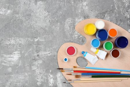 Colorful gouache paints and brushes on grey wooden table Banco de Imagens - 138292998