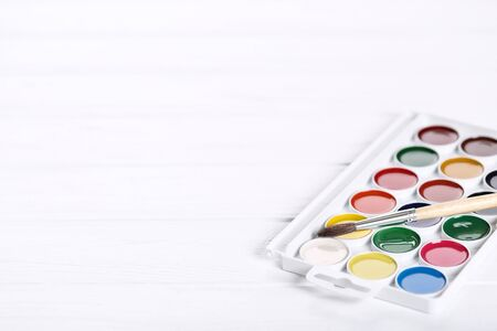Colorful gouache paints and brush on white wooden table