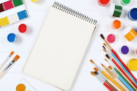 Colorful gouache paints with brushes and blank sheet of paper on white wooden table Banco de Imagens - 138293800