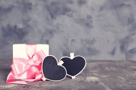 Gift box with ribbon and chalkboards in shape of heart on grey background