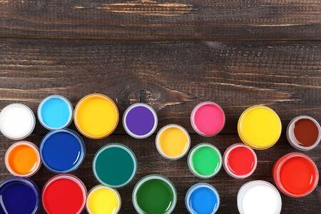 Colorful gouache paints on brown wooden table Banco de Imagens - 138293372