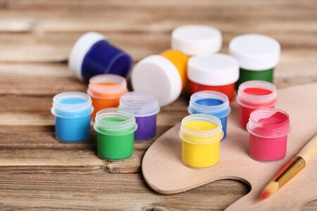 Colorful gouache paints and brushes on brown wooden table Banco de Imagens - 138293438