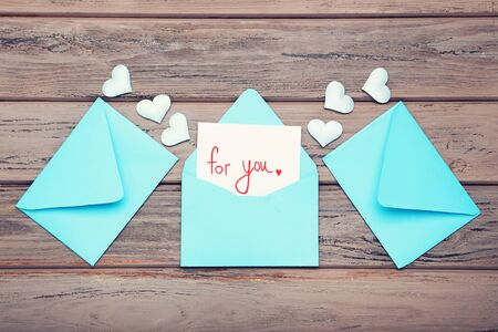 Blue paper envelopes with small hearts and text For You on wooden table