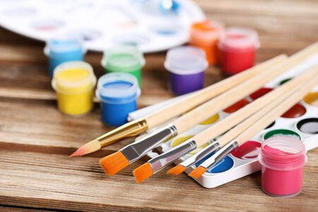 Colorful gouache paints and brushes on brown wooden table Banco de Imagens - 138292746