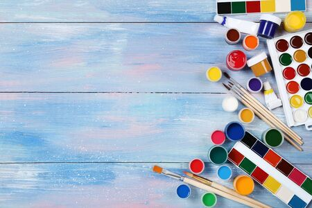 Colorful gouache paints and brushes on blue wooden table